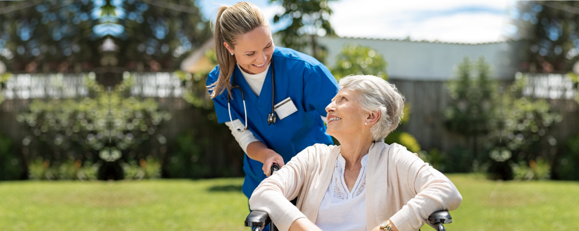 senior woman on a wheelchair while her caregiver is behind her