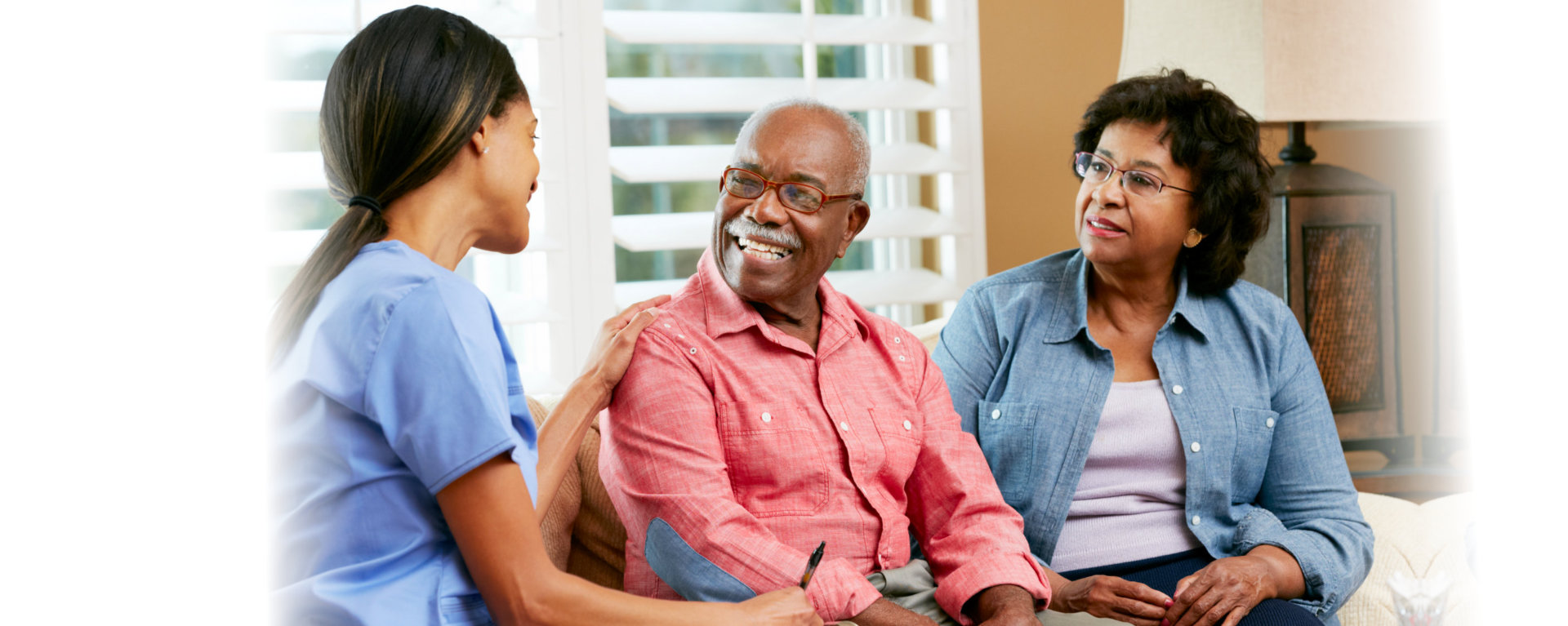 senior counple talking to a caregiver