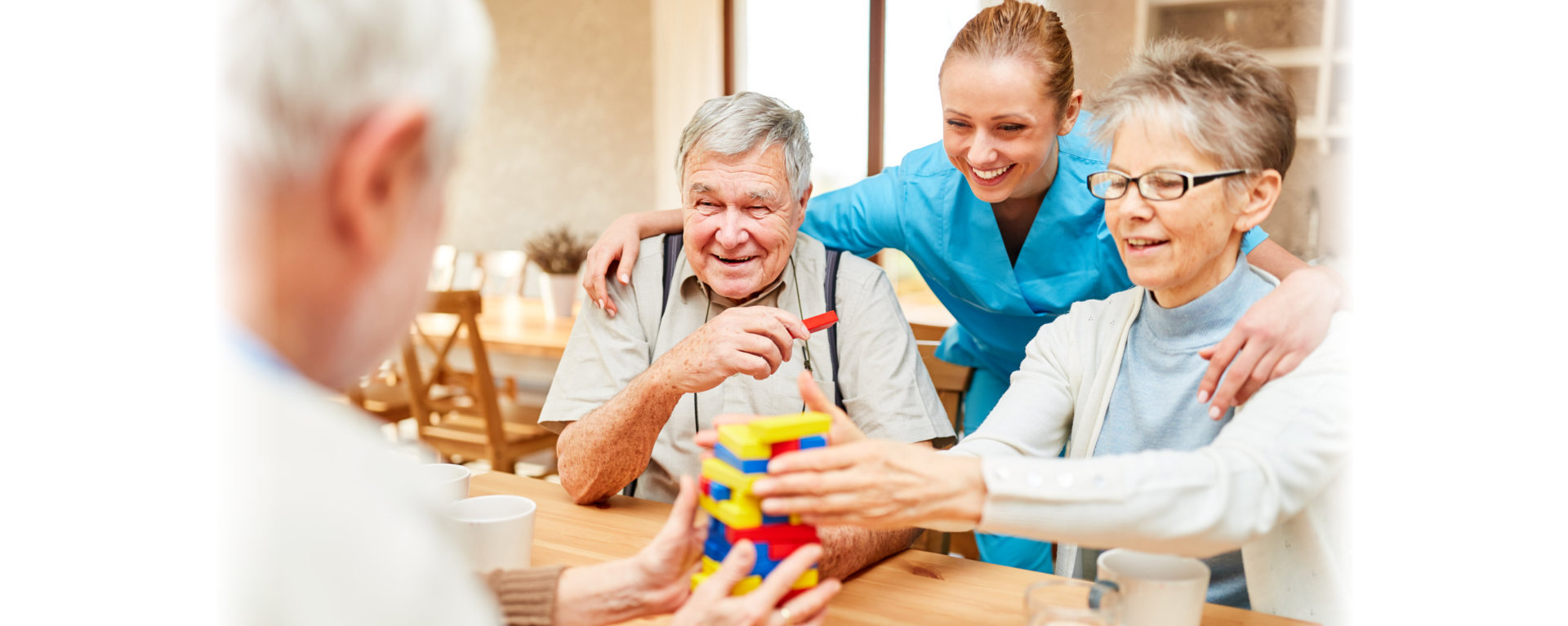 seniors playing blocks with their supportive caregiver