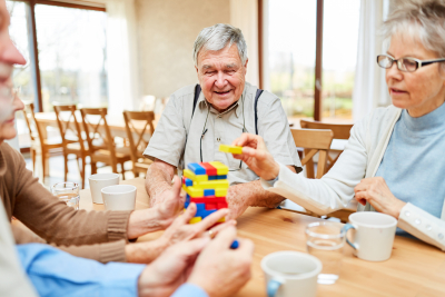group of elderly stack together colorful building blocks as a leisure activity