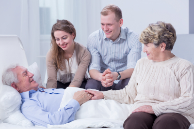 senior man lying in a white hospital bed, surrounded by his smiling relatives