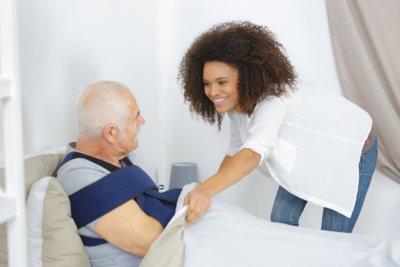 Woman taking care elderly man in nursing home