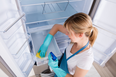 woman cleaning empty refrigerator